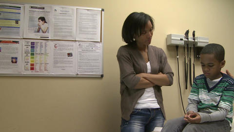 Concerned mom watches doctor examine son Footage