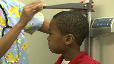 Nurse measures young boys height Footage