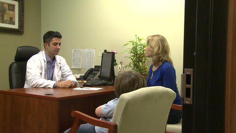 Doctor has office discussion with mother and son Footage