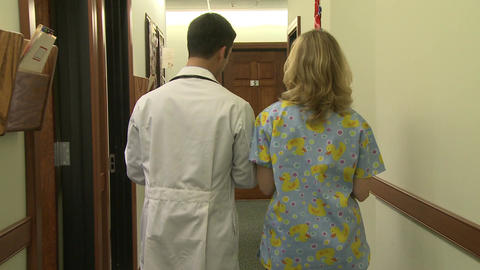 Doctor and nurse walking down hallway Footage
