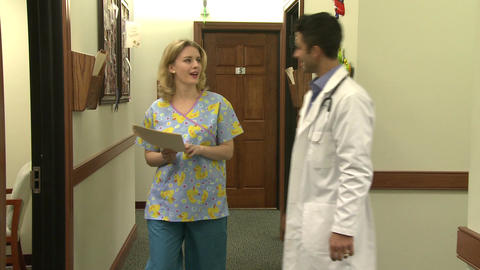 Doctor and nurse have hallway discussion (3 of 6) Footage