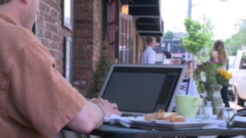 Man typing on his laptop at a sidewalk cafe Footage