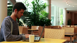Smiling student sitting and using his laptop Footage