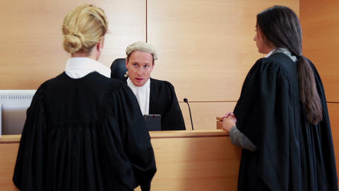 Two lawyers standing and speaking with the judge Footage