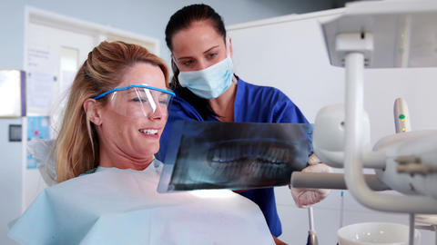 Dentist and patient looking at x-ray together Footage