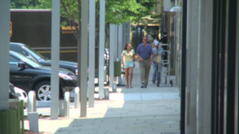 Couple holding hands while walking along storefronts Footage