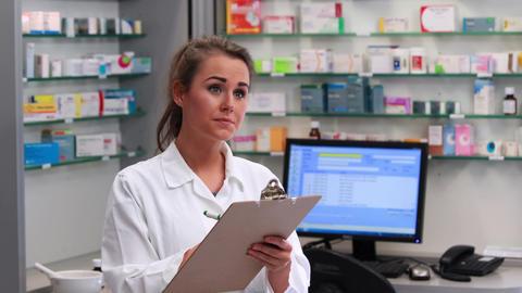 Junior pharmacist writing on clipboard Footage