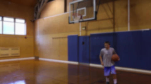 Boy playing indoor basketball alone (2 of 3) Footage