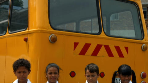 Cute pupils showing thumbs up by bus Footage