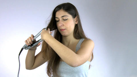 Girl having bad hair day ironing her very long beautiful hair Footage