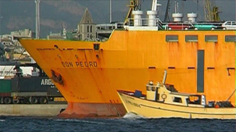 Fishingboat passing yellow ship Stock Video Footage