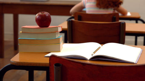 Apple and books on desk in classroom Footage