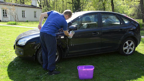 manual hand car wash cleaning with foam and sponge on open air Live Action