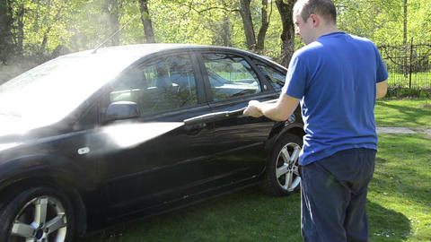 Young man washing his car with strong water jet on open air Footage