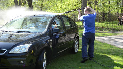 Worker wash black car outdoor with high pressure water equipment Live Action