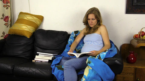 Pregnant woman read book on sofa and caress her stomach belly Footage
