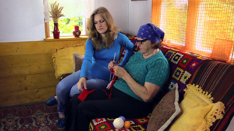 Grandmother teach pregnant granddaughter girl how to knit Footage