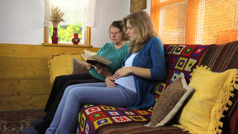 Grandmother and pregnant granddaughter woman read book Footage