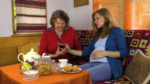pregnant granddaughter show and teach mobile phone to grandma Footage