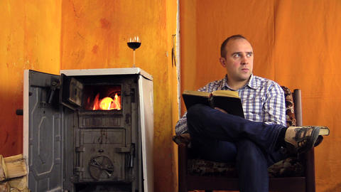 Man read study book near warming stove fire place. Glass of wine Footage