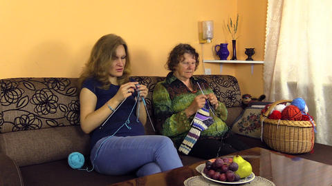 Grandma knitting stockings with pregnant granddaughter on sofa Footage