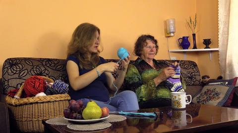 woman wind yarn into ball and grandma finish knit wool sock Footage