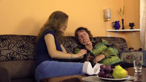 pregnant woman put blood pressure measure tool on grandma hand Footage