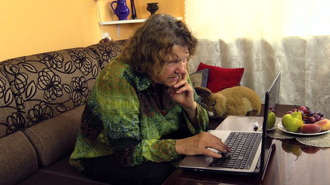 Elderly woman working with laptop notebook computer at home Footage