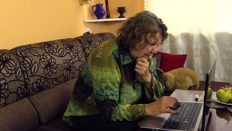 Old grandmother woman working with laptop notebook computer Footage