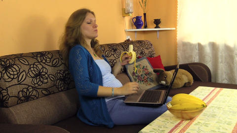 Pregnant woman eat banana fruit work laptop and caress belly Footage