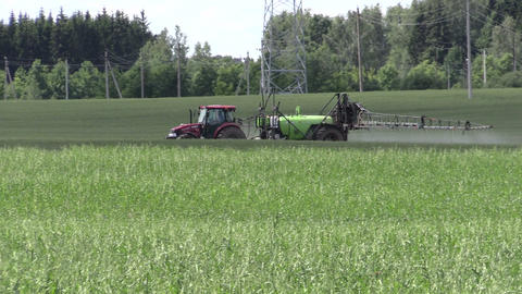 tractor fertilize crop field at herbicides, pesticides. Panning Footage