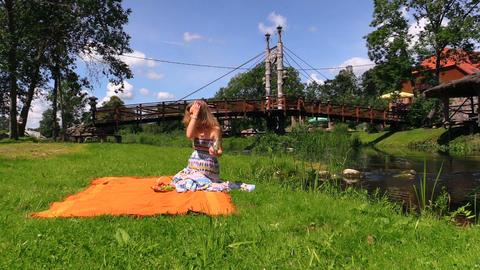 girl with dress sit on rug put fruit glasses near stream bridge Footage