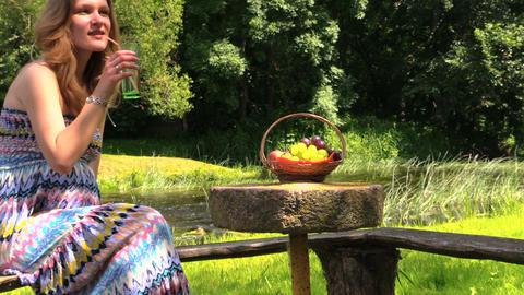 glass water fruit on stone table, girl enjoying warm weather Footage