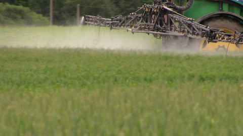 Follow tractor spray field plants with chemical pesticide Footage