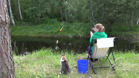 woman catch carp in rural pond. Hungry cat wait for fish Footage