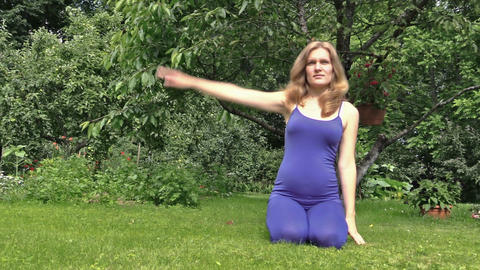 pregnant woman make yoga exercise stretching arms sit on grass Footage