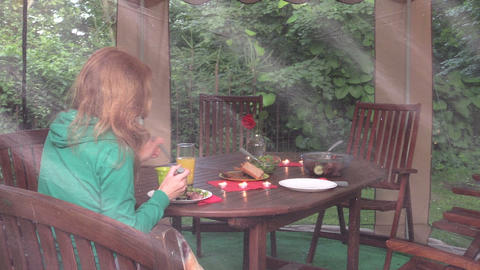 girl eat meat alone in gazebo. Dinner table with candle, flower Footage