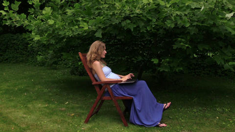pregnant woman enjoy fresh air while work with laptop in garden Live Action