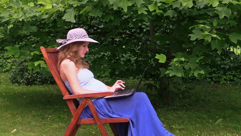 Pregnant woman with hat work with laptop sitting on wooden chair Footage