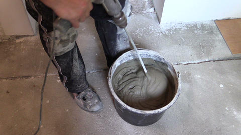 worker mix adhesive cement for tile on bucket with tool Live Action