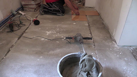 Bucket of cement adhesive glue and man measure tiles on floor Footage