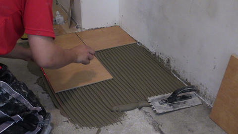 Home improvement handyman laying tile on floor. Zoom in Footage