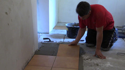 Handyman worker place floor tiles. Home improvement, renovation Footage