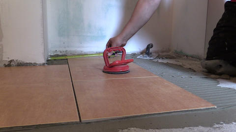 Construction worker man measure and place floor tiles Footage
