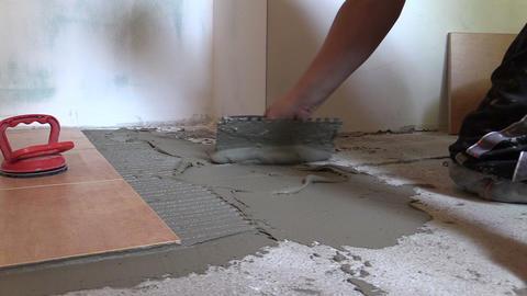Tiler worker hand spread adhesive material. Left side sliding Live Action