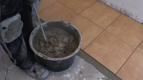 zoom out of man mix cement tile glue on bucket Live Action