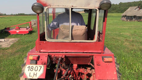 Farmer drive red old tractor between farm building and equipment Footage