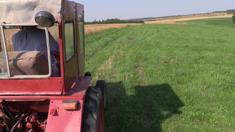 Farmer drive red old tractor between farm rural fields Footage