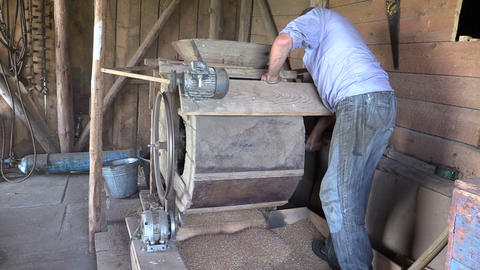 Farmer man spin handle of sifting machine and sift grain in mill Footage