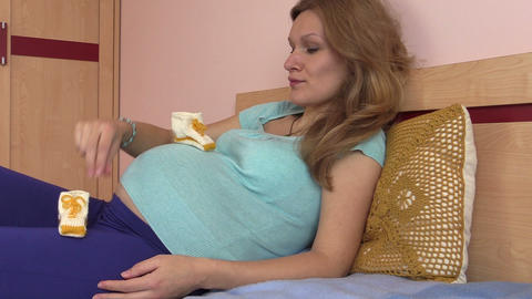 Pregnant woman play with beautiful baby shoes on round stomach Footage